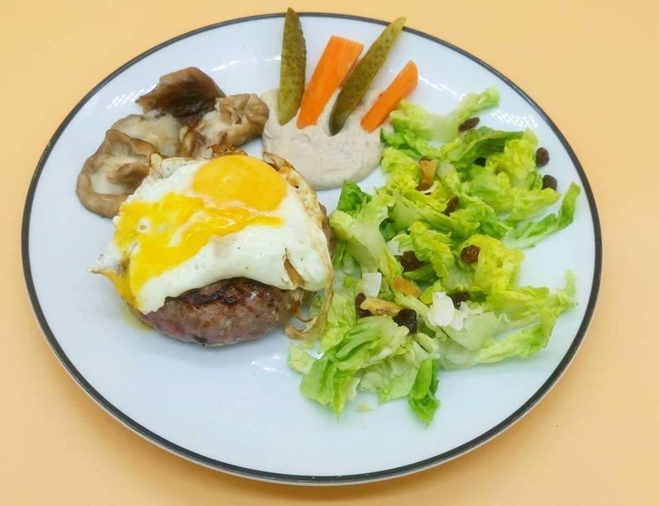 Hamburguesa de carne de pasto con huevo, setas shitake, humus de calabacín y ensalada